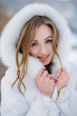 fiatal gyönyörű nő pózol a szabadban télen fehér szőrme kabát