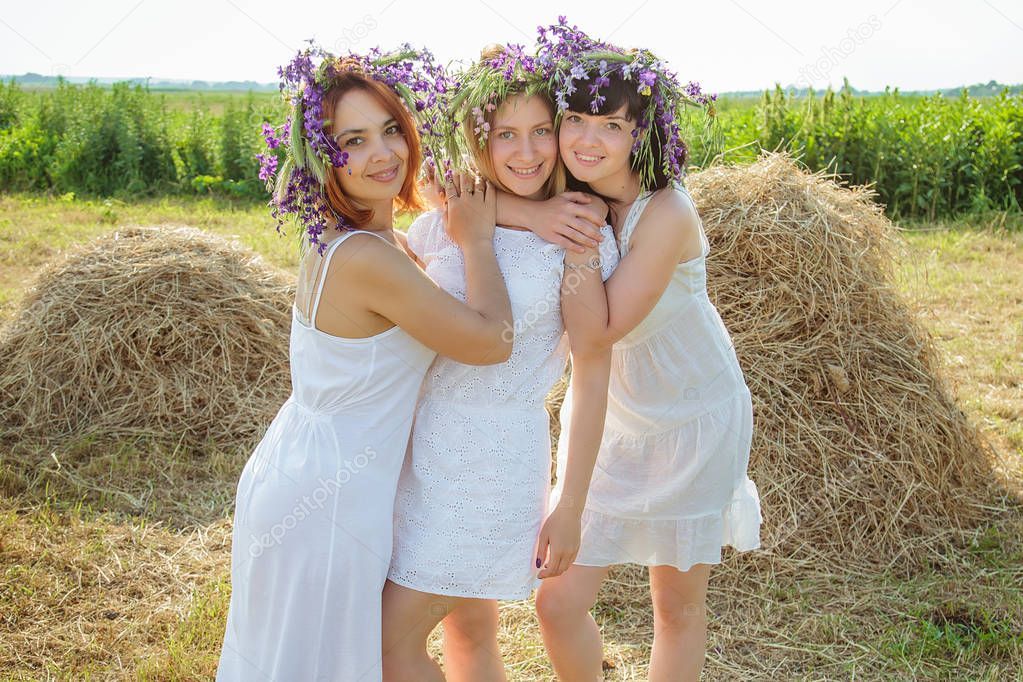 Three young beautiful girls in white dresses and wreaths of wild flowers stayingng near haystack and laughing. Summer in the village