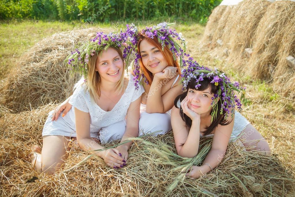 Three young beautiful girls in white dresses and wreaths of wild flowers sitting near haystack. Summer in the village