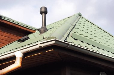 Roof made of metal with a gutter and a drainpipe. Log house with a roof made of iron tiles and a rain gutter, close up side view.