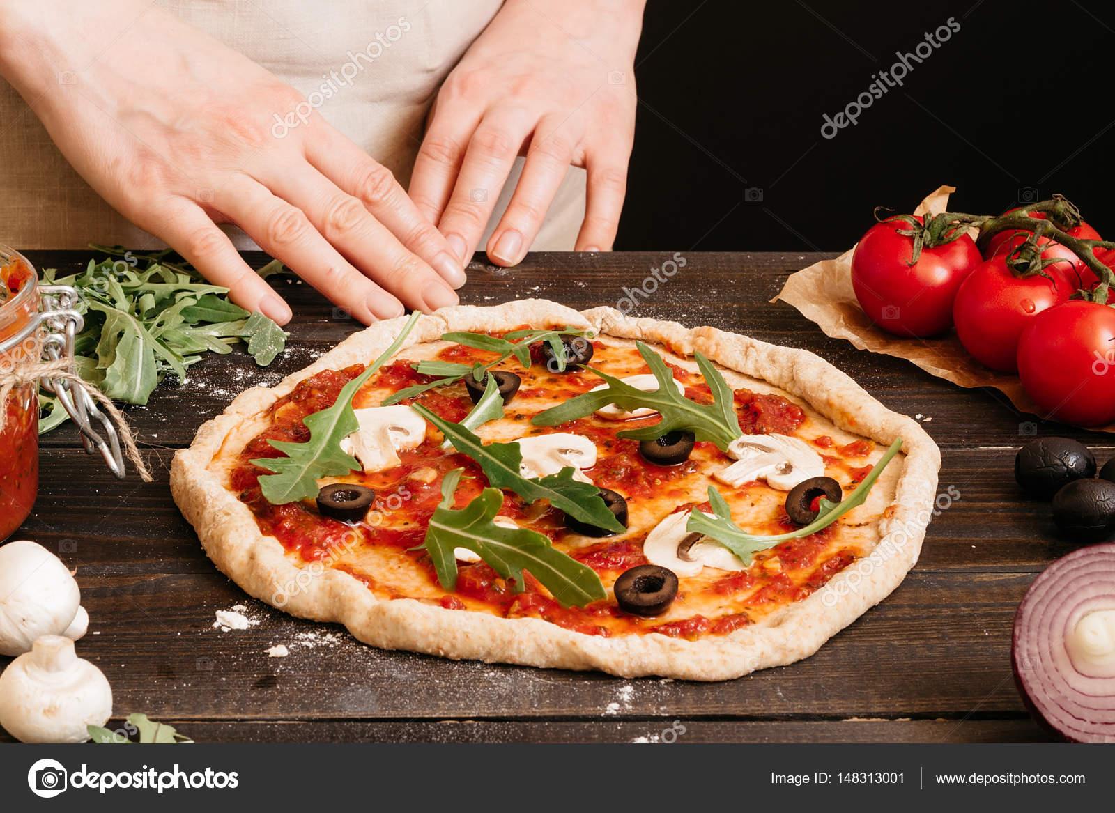 Hände, die Pizza in der Küche kochen. Pizza-Zutaten auf dem ...