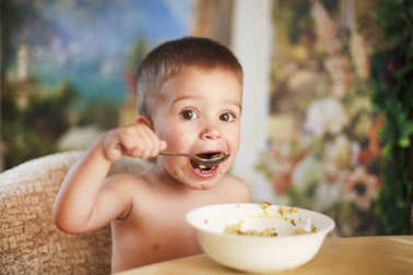 The little boy alone eats at home in the kitchen,