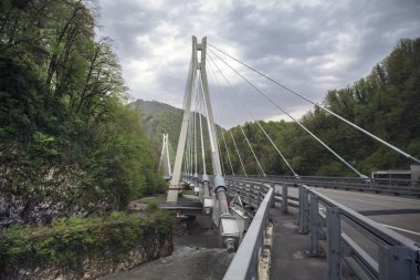 Curved cable-stayed road bridge across the gorge and the river.