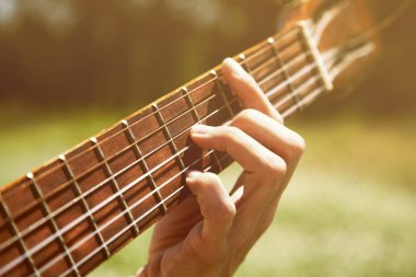 Bar on the guitar close-up, female hand, Hand on fretboard guitar, outdoor, toned