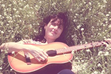 Girl with guitar lying in the grass, toned.