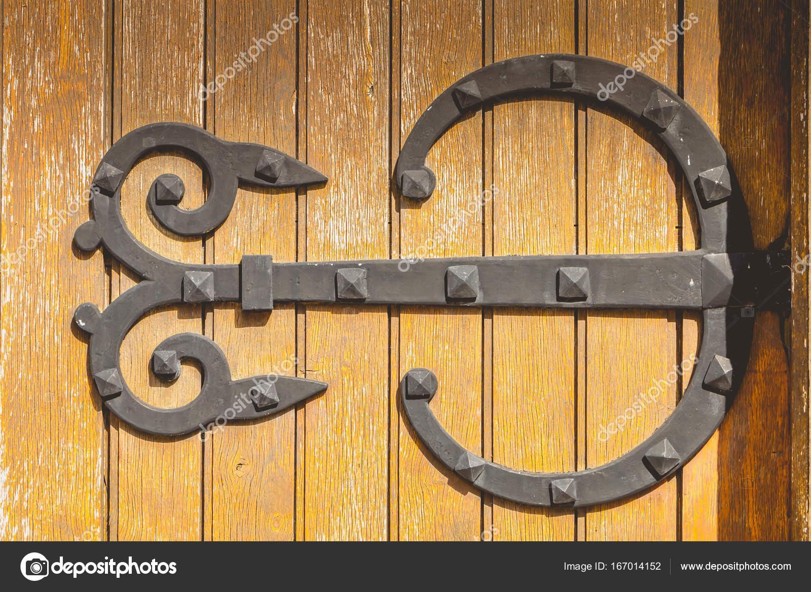 charnière de très grand fer forgé sur une porte en bois à peinture