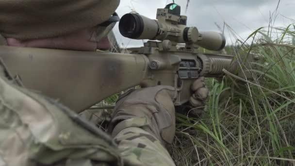 Sniper fekszik mögött fedezi a fű egy pisztolyt a kezében, és lő