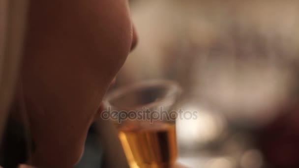 Lány egy kis pohár, egy bárban italok whiskey. Szőke lány ízű konyak sáv