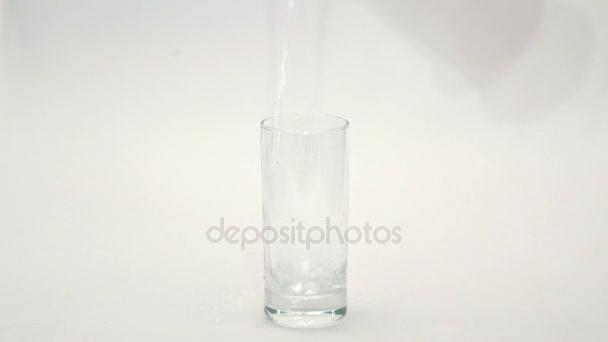 Nalijte vodu do sklenice na bílém pozadí. Voda se nalije do sklenice