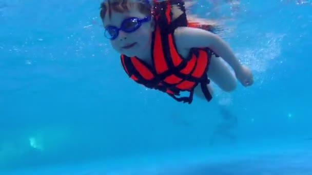 Kind schwimmen unter Wasser-Slow-Motion. Kinder Rettungsweste schwimmt unter Wasser