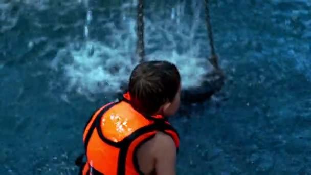 Chlapci hrají v bazénu s vodou. Dítě ve vodě bazénu zpomalené