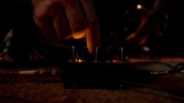 Detailní záběr rukou hudebník ladění tlačítka na ovládání hudby před vystoupením rockové