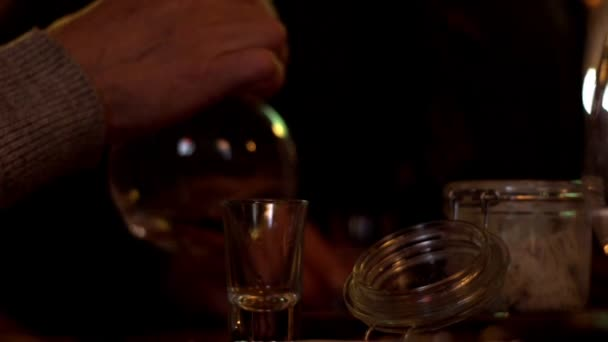 Male hands pouring alcoholic beverage vodka from decanter in glass