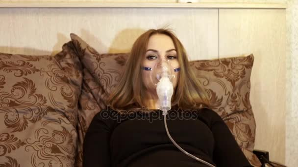 Woman in nebulizer mask making inhalation for asthma treatment