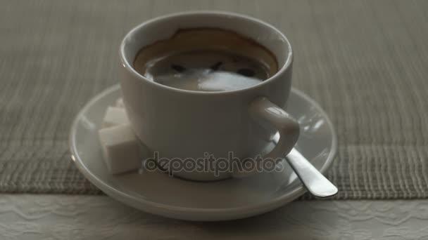 Zblízka bílý šálek černé kávy s cukrem a lžící na talíř stojící na stole
