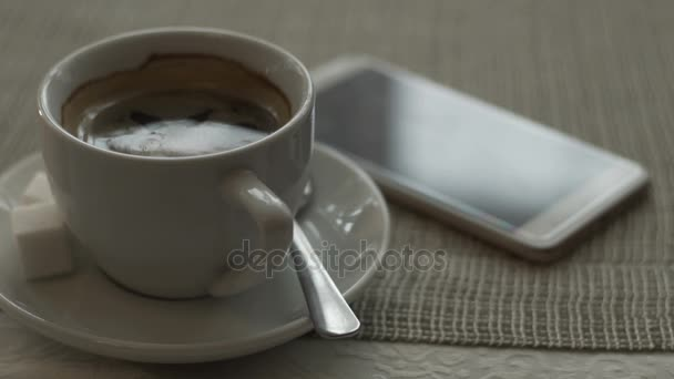 Mobile phone lying beside white cup black coffee on saucer standing on table