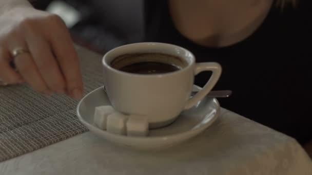 Nő kézzel adjunk hozzá cukrot, a csésze kávé a csészealj állva a táblázat
