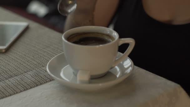 Ženská ruka přidejte cukr a smícháme s lžící šálek kávy stojící na stole