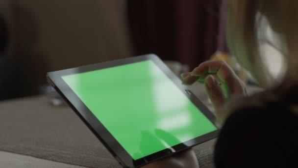 Ženské ruce psaní na zelené obrazovky tablet pc sedí u stolu v kavárně