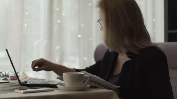 Üzletasszony gépelés-on billentyűzet notebook és írásban napló kávézó