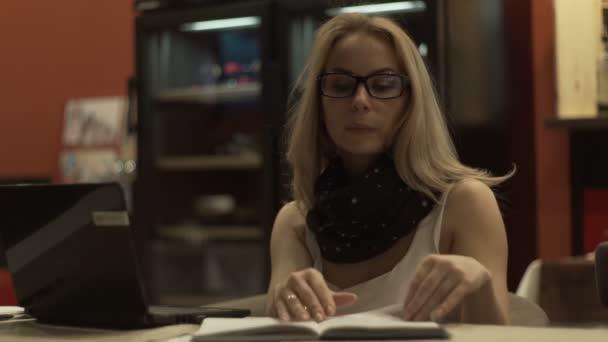 Szép nő, a jegyzetfüzet képernyő látszó szemüveg, és az asztalnál-napló