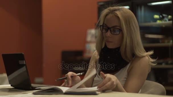 Krásná žena hledá a obracející deník knihy u stolu na pozadí notebook