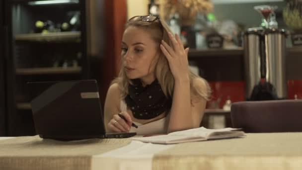 Üzleti nő keresi a jegyzetfüzet képernyő, és írásban napló divatos kávézó