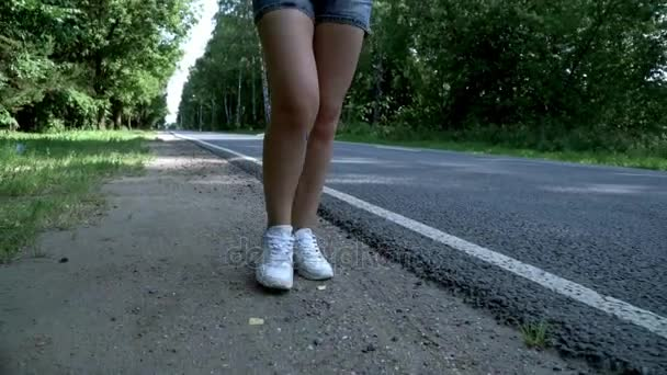 Ženské nohy chůzi po silnici. Žena nohy chůzi na cestě
