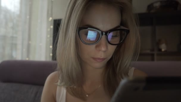Beautiful woman using modern tablet pc and screen reflecting in glasses