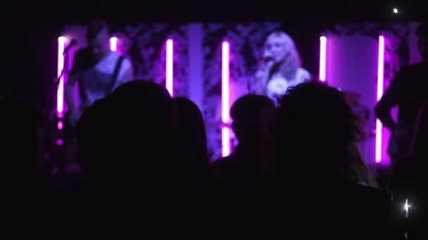 Silueta fanoušky tance v temnu při rockové hudby koncert na jevišti