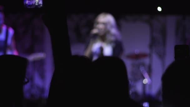 Sziluettjét rajongók táncolni a sötét helyen rock zene koncertet a színpadon