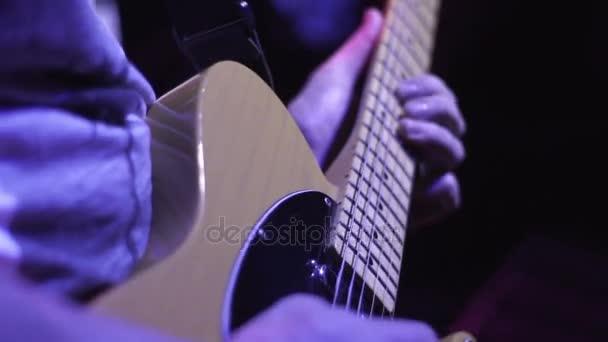 Rockový hudebník hraje na elektrickou kytaru na tmavém pódiu na hudební koncert
