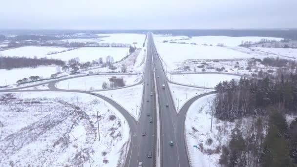 Letecký pohled na osobní a nákladní vozidla pohybující se v sněhu dálniční křižovatka