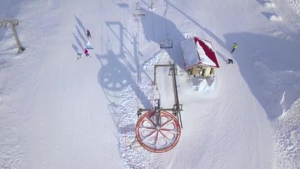 Pohled shora lyžařský vlek na zimní středisko pro dopravu lyžařů a snowboardistů ve sněžných horách. Lidé lyžování na zasněžených horách na letecký pohled na ski resort.