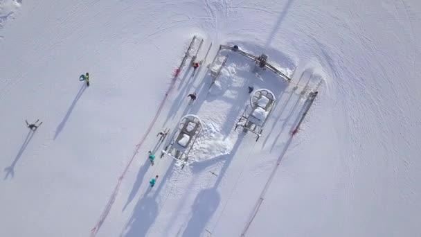 Lyžařský vlek na zimní středisko pro dopravu lyžařů a snowboardistů na sněhu hory DRONY. Lidé lyžování na zasněžených horách na letecký pohled na ski resort.