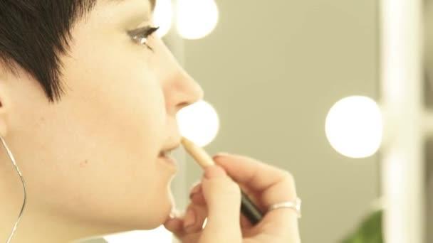 close up face woman doing make up lips with pencil close up. Erwachsene Frau trägt Lippenstift auf Lippen vor Make-up-Spiegel mit Licht.