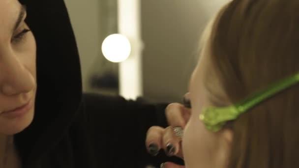 Nő smink művész alkalmazása Alapítvány krém a bőr arc divat modell közelről. Professzionális arc smink, fiatal nő, kozmetikai szalon.