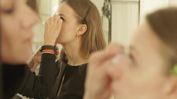 Žena maskérka pomocí kosmetiky houba pro používání základ krému na žena kůži kolem očí zblízka. Žena tvář make-up v profesionální kosmetické studio