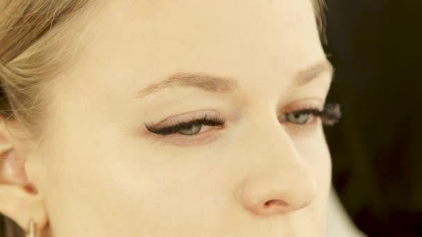 Detailní záběr obličeje mladá žena během použití make-upu s houbou kosmetika na pleť beauty studio. Profesionální make-up pro korekce pleťových odstínů v šatně