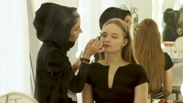 Žena vizážistiku dělá make-up obočí na obličej mladé model studio krásy. Žena vizážistiku barvení obočí na obličej make-up modelu přední zrcátko v šatně