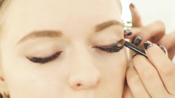 Žena používající kosmetické štětce pro líčení očí krásu modelu. Detailní záběr vizážistka dělá make-up očí pro krásnou ženu