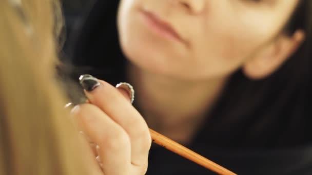 Elegán make-up pomocí štětce pro použití kosmetiky na kůži obličeje žena modelka v kosmetické studio. Profesionální make-up žena tvář