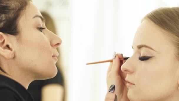 Woman make up artist using cosmetics brush for makeup eyes beauty model. Close up visagist doing makeup face for beautiful woman.