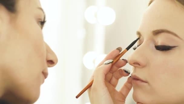 Ženy tvoří umělec pomocí kosmetické štětce pro líčení očí a obočí pro krásu modelu. Detailní záběr vizážistka dělá tvář make-up pro krásnou ženu