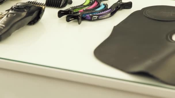 Hairdressing scissors, hair clipper, hair clips, tools and accessories on table in hair salon close up. Working tools in barber shop.