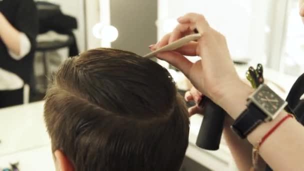 Žena česání mužské vlasy hřebenem a kropení vodou pro Kadeřnické studio krásy kadeřnice. Aby účes kadeřnice v holičství