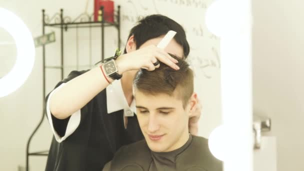 Professional hair stylist cutting hair in barber shop. Woman hairdresser cutting male hair with electric shaver front mirror in beauty salon.