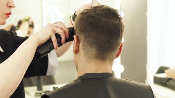 Haircutter mužské vlasy cut s zastřihovač vlasů a hřeben v kadeřnictví zblízka. Kadeřník dělá profesionální účes s elektrický holicí strojek