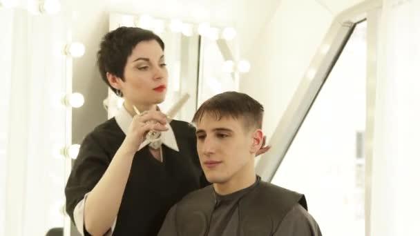 Žena kadeřník česání vlasy před řezáním s nůžky v holičství. Haircutter dělá mužský účes s hřeben a Kadeřnické nůžky v beauty studio