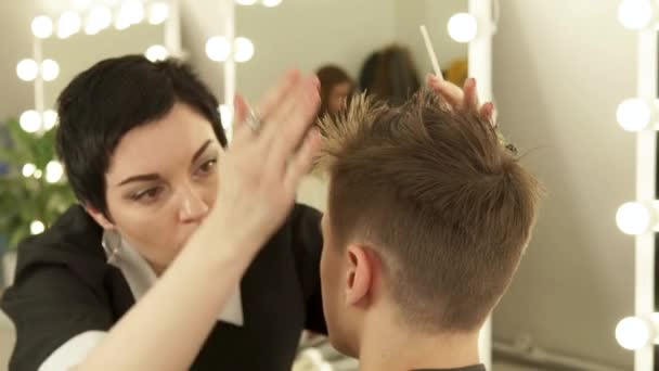 Woman hairdresser finish hair male style. Haircutter combing male hair after cutting in hairdressing salon. Woman hairstylist working with client in barbershop.